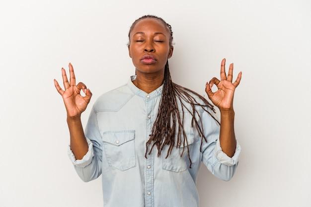 Jeune femme afro-américaine isolée sur fond blanc se détend après une dure journée de travail, elle fait du yoga.