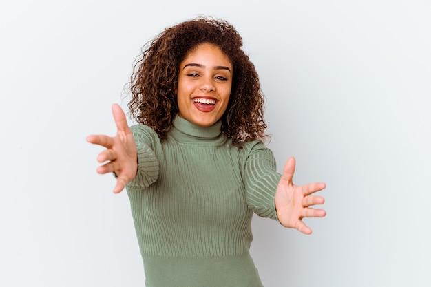 Jeune femme afro-américaine isolée sur fond blanc se sent confiant en donnant un câlin à la caméra.