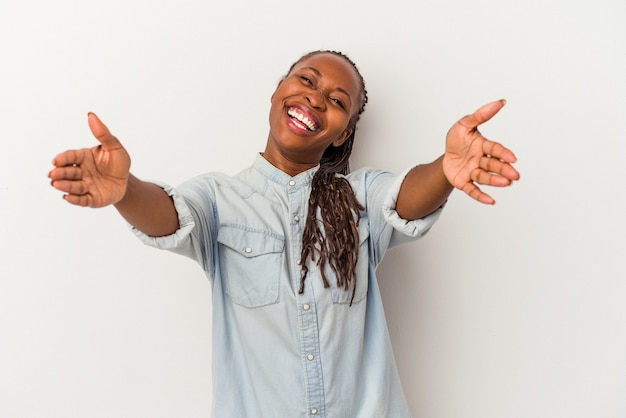 Jeune femme afro-américaine isolée sur fond blanc se sent confiante en donnant un câlin à la caméra.