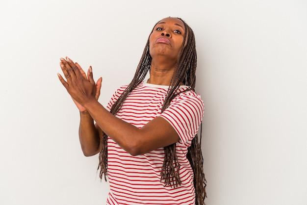 Jeune femme afro-américaine isolée sur fond blanc se sentant énergique et confortable, se frottant les mains confiantes.