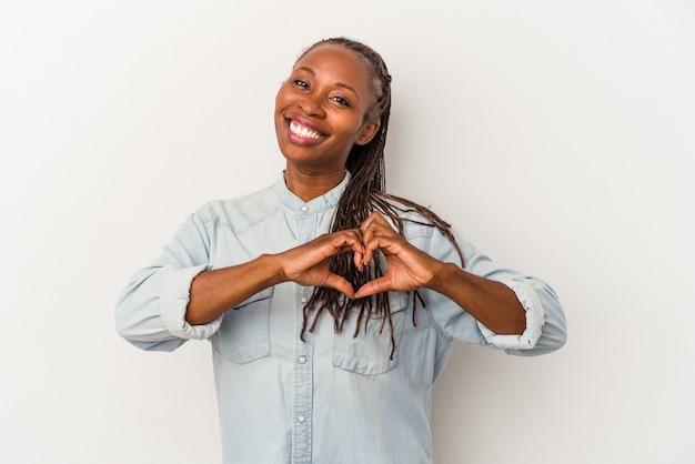 Jeune femme afro-américaine isolée sur fond blanc souriant et montrant une forme de coeur avec les mains.