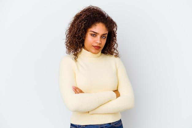 Jeune femme afro-américaine isolée sur fond blanc suspecte, incertaine, vous examinant.