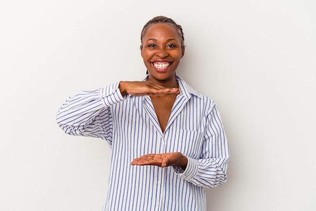 Jeune femme afro-américaine isolée sur fond blanc tenant quelque chose à deux mains, présentation du produit.