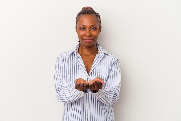 Jeune femme afro-américaine isolée sur fond blanc tenant quelque chose avec des paumes, offrant à la caméra.