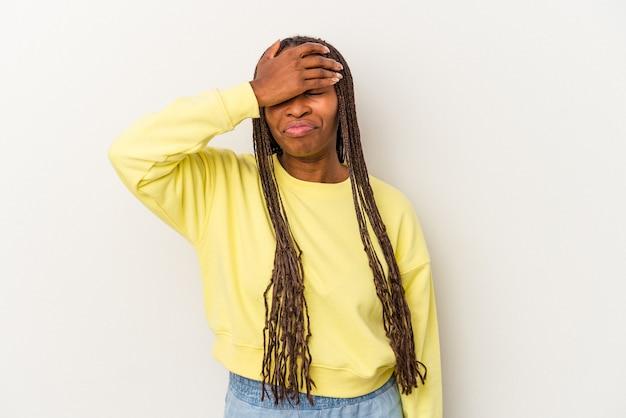 Jeune femme afro-américaine isolée sur fond blanc touchant les temples et ayant des maux de tête.