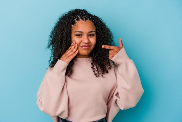 Jeune femme afro-américaine isolée sur fond bleu ayant une forte douleur dentaire, une douleur molaire.