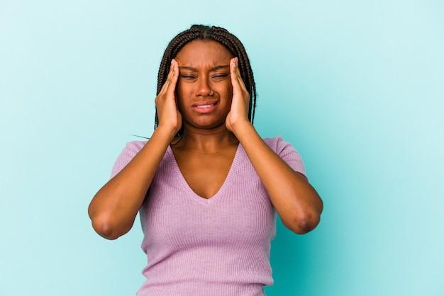 Jeune femme afro-américaine isolée sur fond bleu ayant un mal de tête, touchant le devant du visage.
