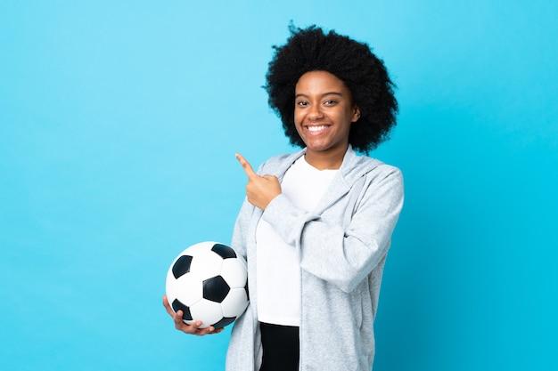 Jeune femme afro-américaine isolée sur fond bleu avec ballon de foot et pointant vers le côté