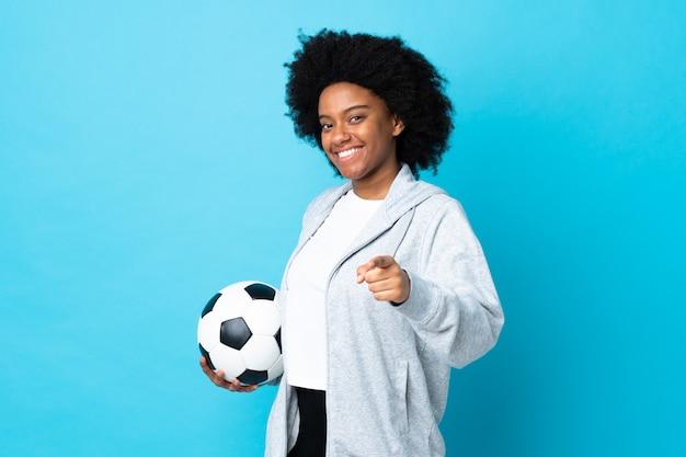 Jeune femme afro-américaine isolée sur fond bleu avec un ballon de soccer et pointant vers l'avant