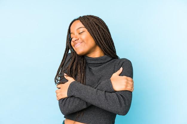 Jeune femme afro-américaine isolée sur fond bleu câlins, souriant insouciant et heureux.