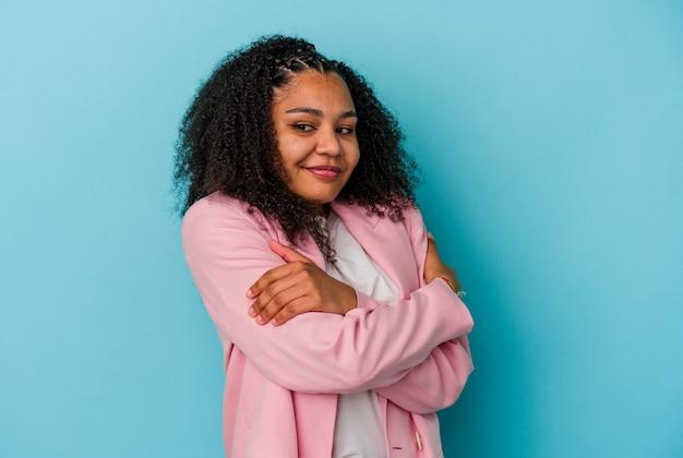 Jeune femme afro-américaine isolée sur fond bleu câlins, souriante insouciante et heureuse.