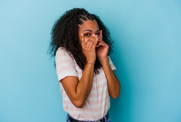 Jeune femme afro-américaine isolée sur fond bleu clignote à travers les doigts effrayés et nerveux.