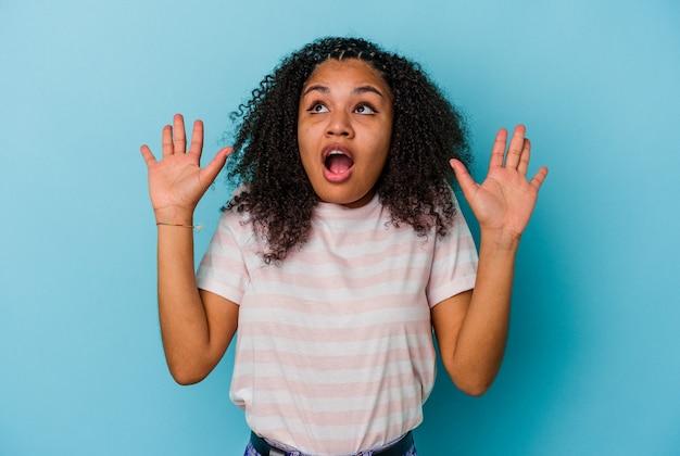 Jeune femme afro-américaine isolée sur fond bleu criant vers le ciel, levant les yeux, frustrée.