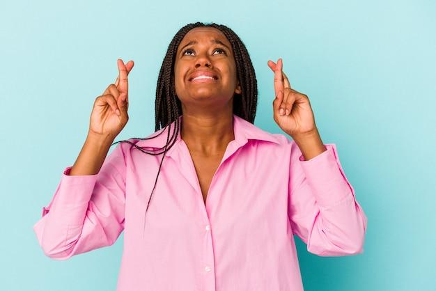 Jeune femme afro-américaine isolée sur fond bleu croisant les doigts pour avoir de la chance