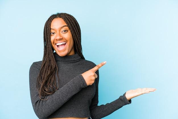 Jeune femme afro-américaine isolée sur fond bleu excité tenant un espace de copie sur la paume.