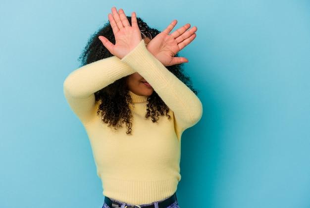 Jeune femme afro-américaine isolée sur fond bleu en gardant les deux bras croisés, concept de déni.