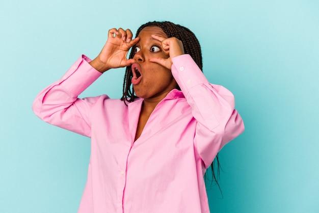 Jeune femme afro-américaine isolée sur fond bleu en gardant les yeux ouverts pour trouver une opportunité de réussite.