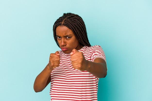 Jeune femme afro-américaine isolée sur fond bleu jetant un coup de poing, colère, combat à cause d'une dispute, boxe.