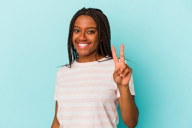 Jeune femme afro-américaine isolée sur fond bleu joyeuse et insouciante montrant un symbole de paix avec les doigts.