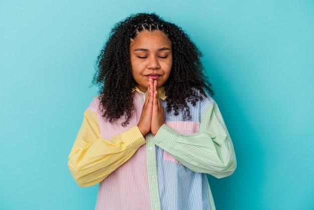 Jeune femme afro-américaine isolée sur fond bleu, main dans la main en priant près de la bouche, se sent en confiance.