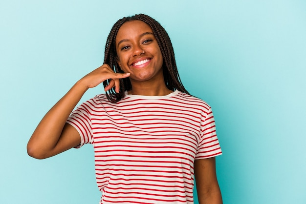 Jeune femme afro-américaine isolée sur fond bleu montrant un geste d'appel de téléphone portable avec les doigts.