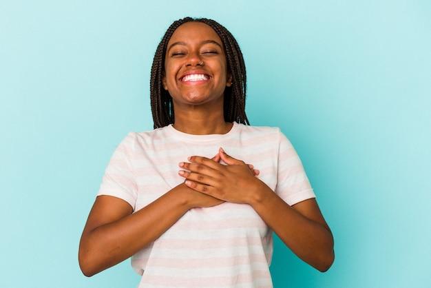 Jeune femme afro-américaine isolée sur fond bleu en riant en gardant les mains sur le cœur, concept de bonheur.