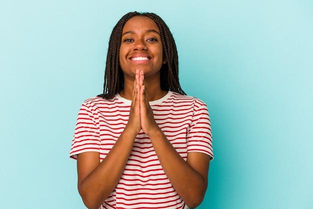 Jeune femme afro-américaine isolée sur fond bleu, tenant la main en prière près de la bouche, se sent confiante.