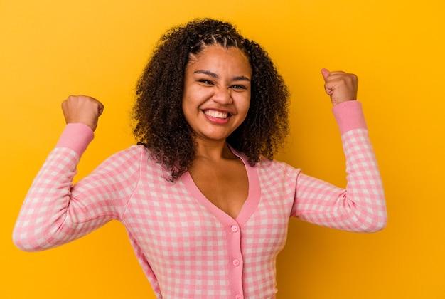 Jeune femme afro-américaine isolée sur fond jaune acclamant insouciante et excitée. notion de victoire.