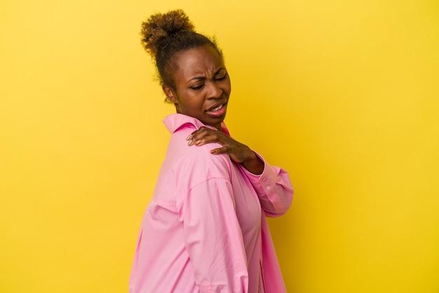 Jeune femme afro-américaine isolée sur fond jaune ayant une douleur à l'épaule.