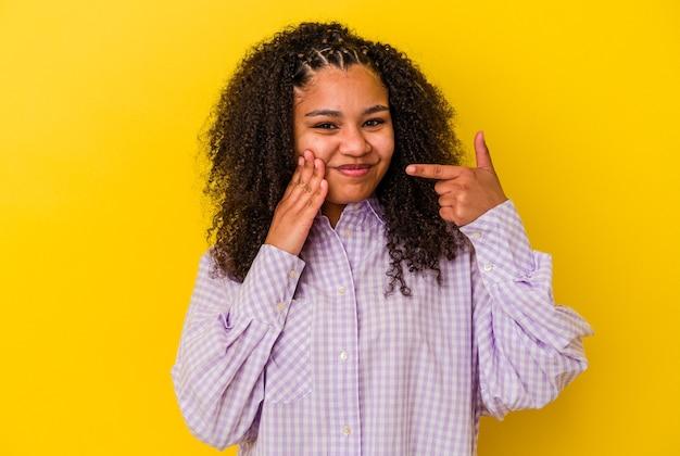 Jeune femme afro-américaine isolée sur fond jaune ayant une forte douleur dentaire, une douleur molaire.