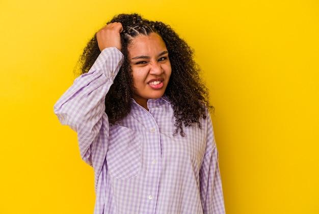 Jeune femme afro-américaine isolée sur fond jaune célébrant une victoire, une passion et un enthousiasme, une expression heureuse.