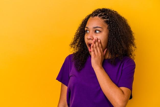 Jeune femme afro-américaine isolée sur fond jaune choquée à cause de quelque chose qu'elle a vu.