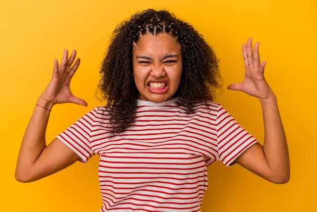 Jeune femme afro-américaine isolée sur fond jaune criant de rage.