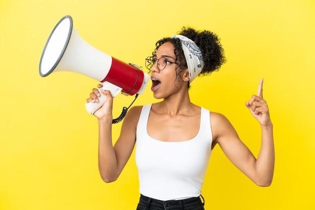 Jeune femme afro-américaine isolée sur fond jaune criant à travers un mégaphone pour annoncer quelque chose en position latérale