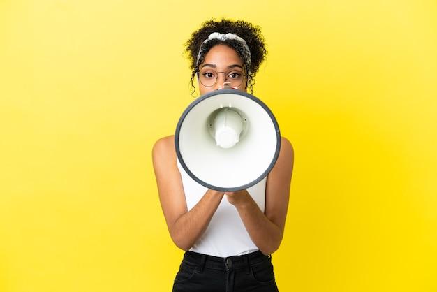 Jeune femme afro-américaine isolée sur fond jaune criant à travers un mégaphone pour annoncer quelque chose