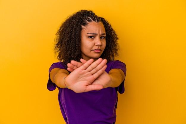 Jeune femme afro-américaine isolée sur fond jaune debout avec la main tendue montrant un panneau d'arrêt, vous empêchant.