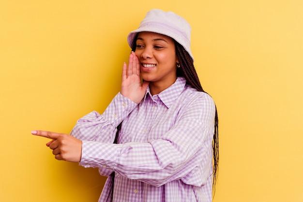Jeune femme afro-américaine isolée sur fond jaune disant un potin, pointant vers le côté rapportant quelque chose.