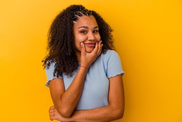 Jeune femme afro-américaine isolée sur fond jaune, doutant entre deux options.