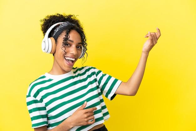 Jeune femme afro-américaine isolée sur fond jaune, écoutant de la musique et faisant un geste de guitare