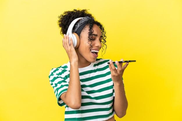 Jeune femme afro-américaine isolée sur fond jaune, écoutant de la musique avec un mobile et chantant