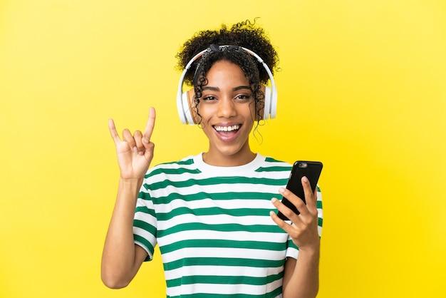 Jeune femme afro-américaine isolée sur fond jaune, écoutant de la musique avec un mobile faisant un geste rock