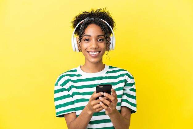 Jeune femme afro-américaine isolée sur fond jaune, écoutant de la musique avec un mobile et regardant devant