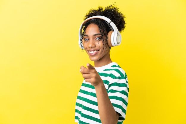 Jeune femme afro-américaine isolée sur fond jaune, écoutant de la musique et pointant vers l'avant
