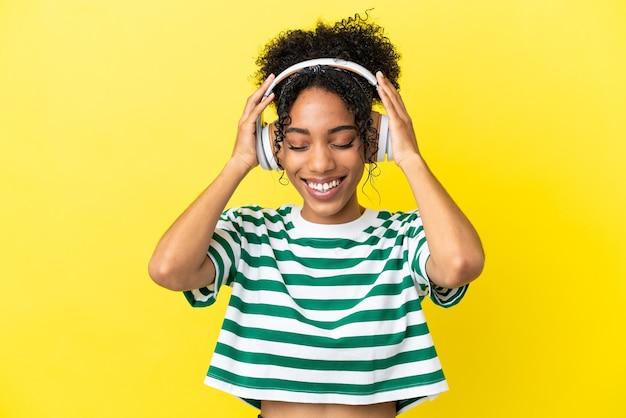 Jeune femme afro-américaine isolée sur fond jaune, écouter de la musique