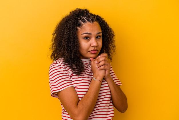 Jeune femme afro-américaine isolée sur fond jaune effrayée et effrayée.