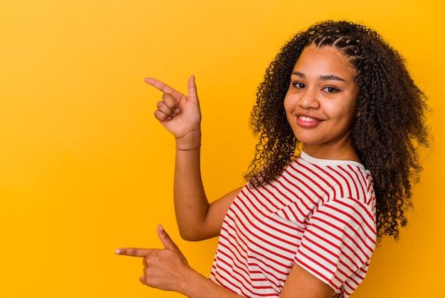 Jeune femme afro-américaine isolée sur fond jaune excité pointant avec les index loin.