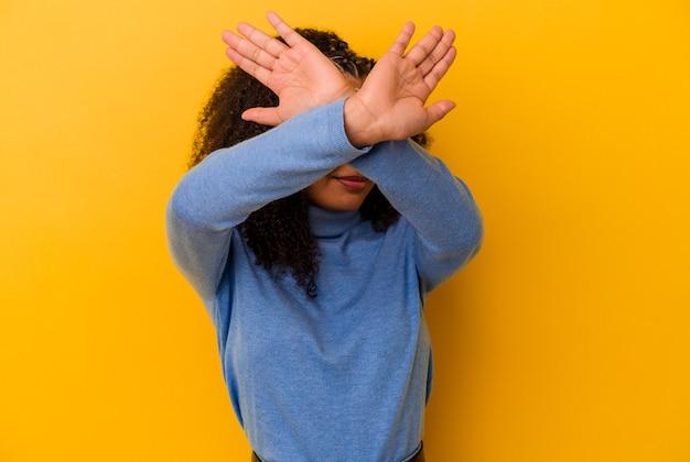 Jeune femme afro-américaine isolée sur fond jaune en gardant les deux bras croisés, concept de déni.