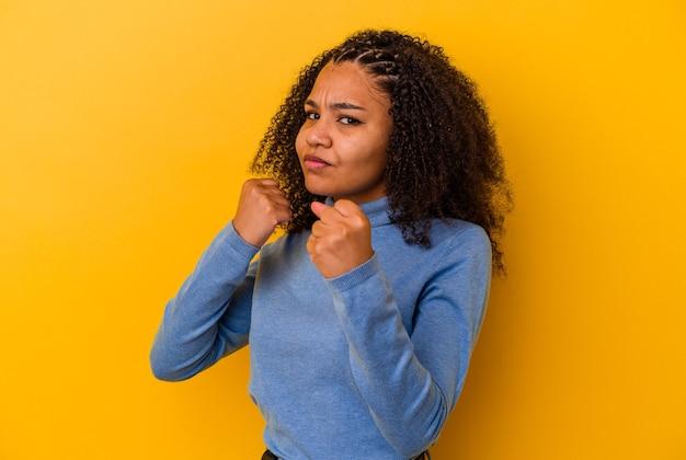 Jeune femme afro-américaine isolée sur fond jaune jetant un coup de poing, la colère, les combats en raison d'une dispute, la boxe.