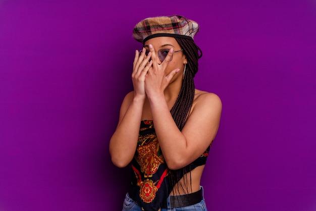 Jeune femme afro-américaine isolée sur fond jaune jeune femme afro-américaine isolée sur fond jaune clignote à travers les doigts effrayés et nerveux.