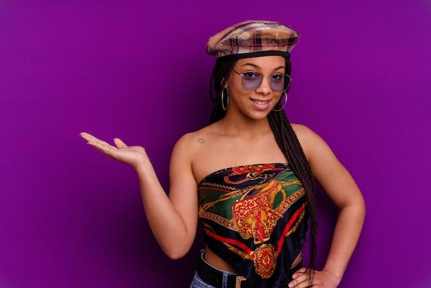 Jeune Femme Afro-américaine Isolée Sur Fond Jaune Jeune Femme Afro-américaine Isolée Sur Fond Jaune Montrant Un Espace De Copie Sur Une Paume Et Tenant Une Autre Main Sur La Taille. Photo Premium